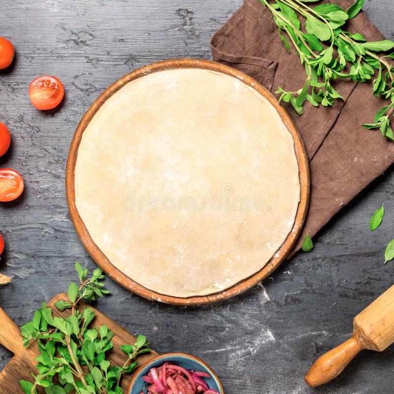 与集合成份的未加工的薄饼面团烹调的素食pizz 免版税库存照片