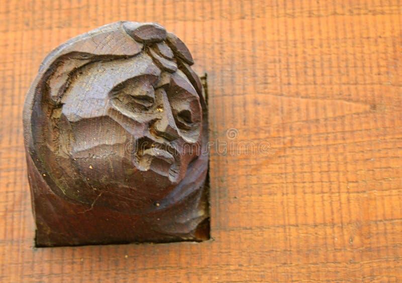 与雕刻的老木门以头的形式 库存照片