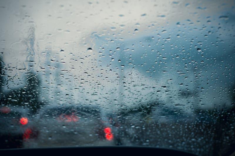 与雨下落的车窗在玻璃或挡风玻璃,被弄脏的交通在雨天在城市 免版税库存照片