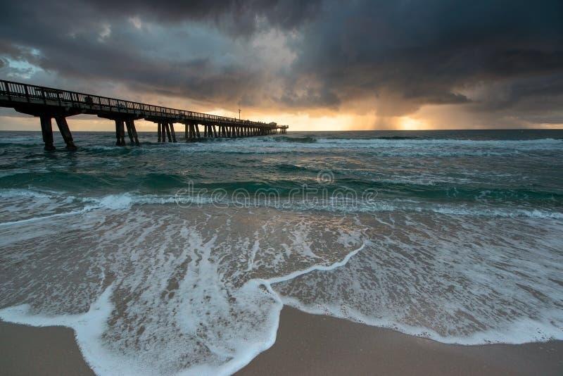 与雨的日出在海洋。 免版税库存图片