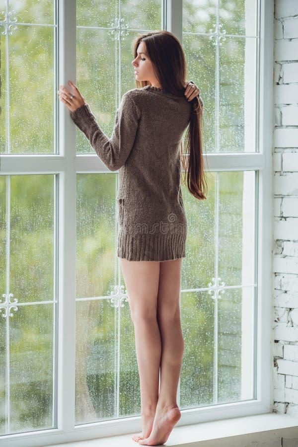 与雨的美丽的少妇站立的单独近的窗口滴下 有长的亭亭玉立的腿的性感和哀伤的女孩 概念  免版税库存照片