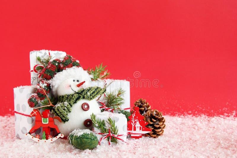 与雪人和礼物盒的圣诞节静物画在与人为雪的红色背景 免版税库存图片