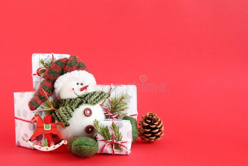与雪人和礼物盒的圣诞节静物画在红色背景、装饰的冷杉分支、杉木锥体和木装饰 图库摄影