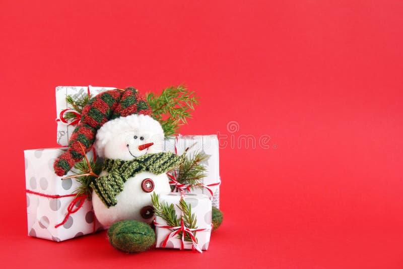 与雪人和礼物盒的圣诞节静物画在红色背景,装饰冷杉分支 库存图片
