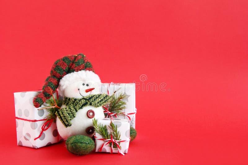 与雪人和礼物盒的圣诞节静物画在红色背景,装饰冷杉分支 图库摄影