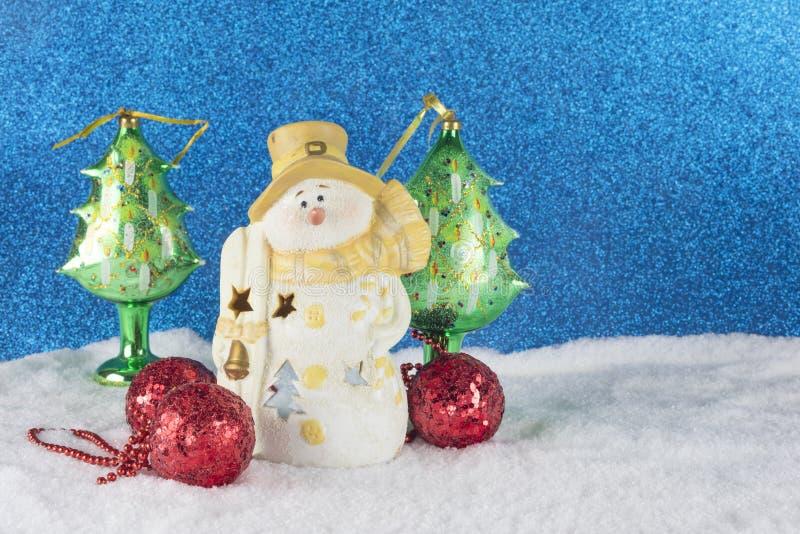 与雪人小雕象,在sno的红色中看不中用的物品的圣诞节装饰 库存照片