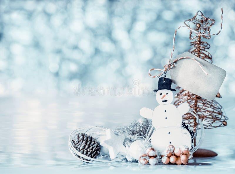 与雪人,标记嘲笑的卡片和在蓝色bokeh背景的圣诞树 库存图片