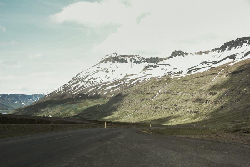 与雪和路的山景在夏天在冰岛-阴天,远足的愉快 库存照片
