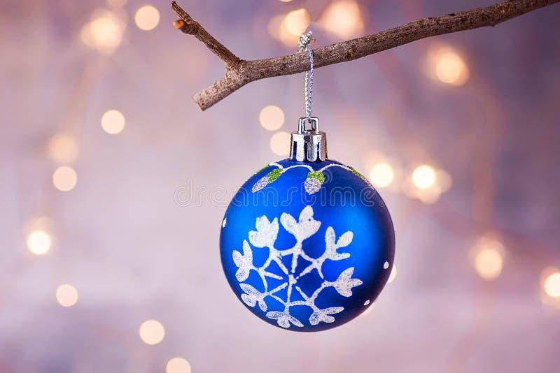 与雪垂悬在分支的剥落装饰品的蓝色圣诞树球 光亮的诗歌选金黄光 库存照片