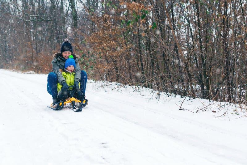 与雪撬的愉快的家庭在获得的冬天乐趣一起 儿童sledding 愉快的享受雪橇乘驾的母亲和她的儿子 家庭驾驶 库存照片