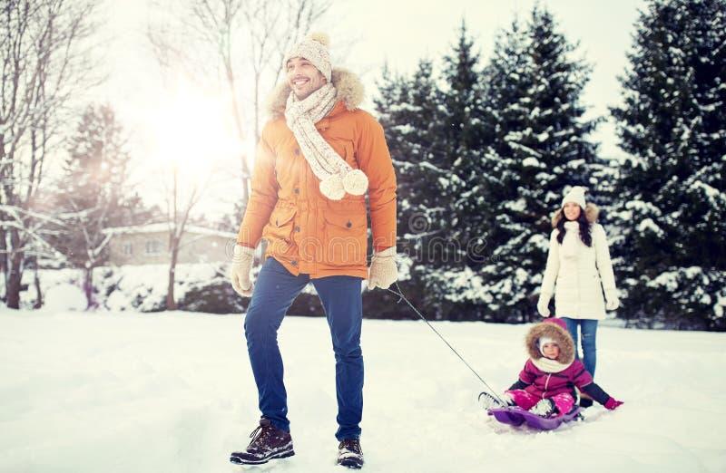 与雪撬的愉快的家庭走在冬天的户外 免版税库存图片