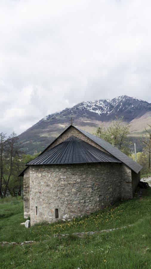 与雪海角的小石教堂黑山山 近对Plav湖和绿草 库存照片