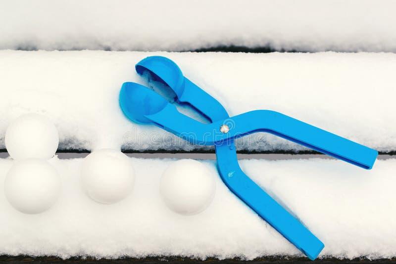 与雪球制造商的雪球 孩子与雪的冬天比赛 雪球比赛 免版税库存图片