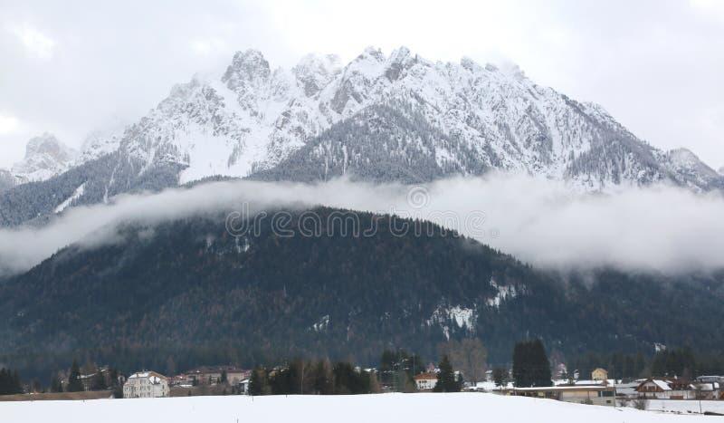 与雪的伟大的山在北Ital的多比亚科镇附近 图库摄影