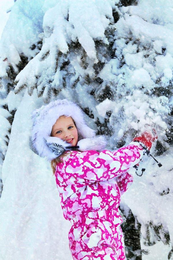 与雪的冬天衣裳的儿童女孩的在树附近在公园 免版税库存图片