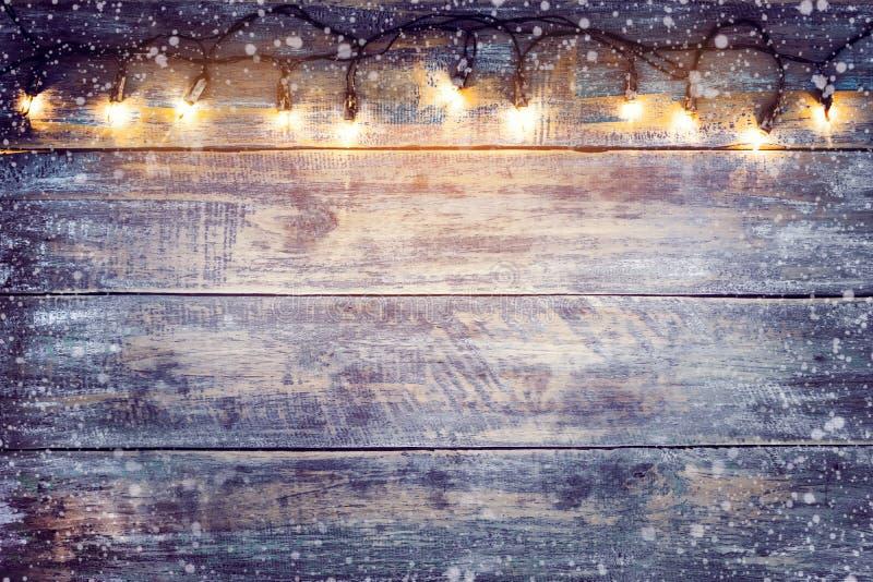 与雪的圣诞灯电灯泡在木桌上 库存照片