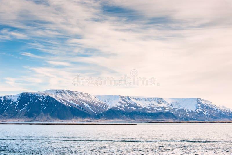 与雪的山在海洋 免版税库存照片