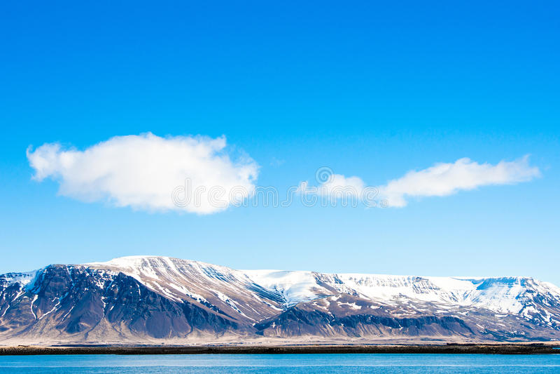 与雪的山由海洋 免版税库存图片