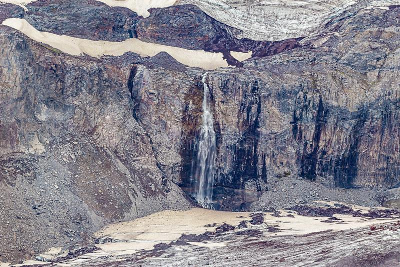 与雪的崎岖的峭壁熔化入瀑布的面孔和冰 免版税库存图片