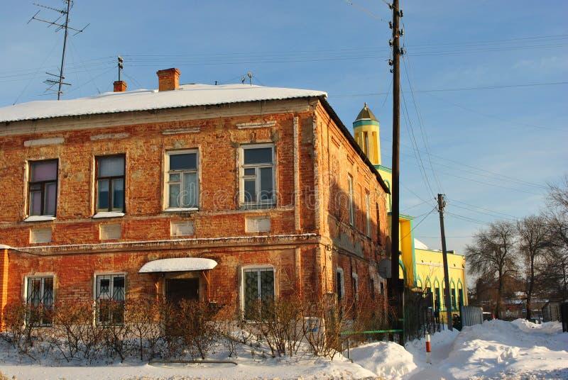 与雪的红砖两商店居民住房在屋顶,与黄色教会的城市风景背景的 免版税库存照片