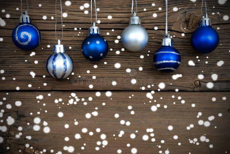 与雪的蓝色和银色圣诞节球 库存照片