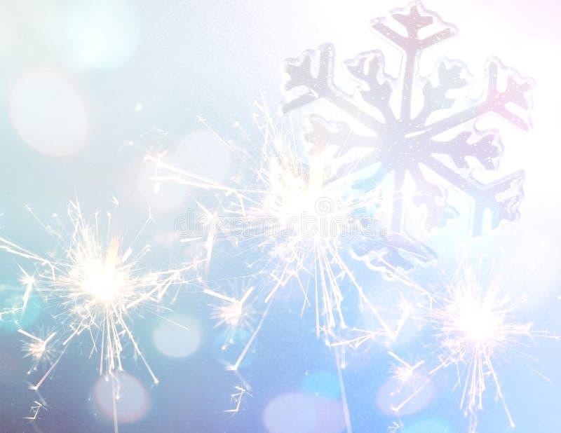 与雪花标志的闪烁发光物在蓝色闪烁圣诞节背景 免版税图库摄影