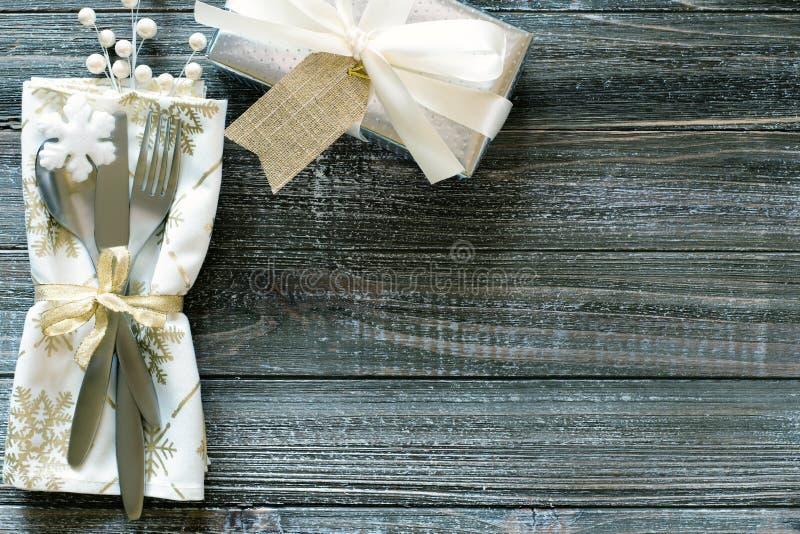 与雪花餐巾的冷漠的圣诞节表餐位餐具,与白色弓的银色礼物和莓果,全部在土气木backgrou 免版税库存图片