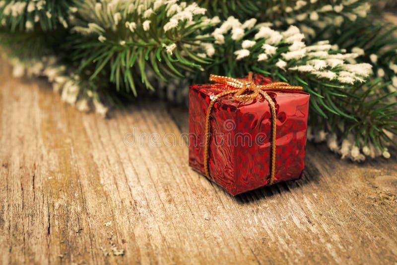 与雪,在葡萄酒木头的红色礼物盒的云杉的分支 免版税图库摄影