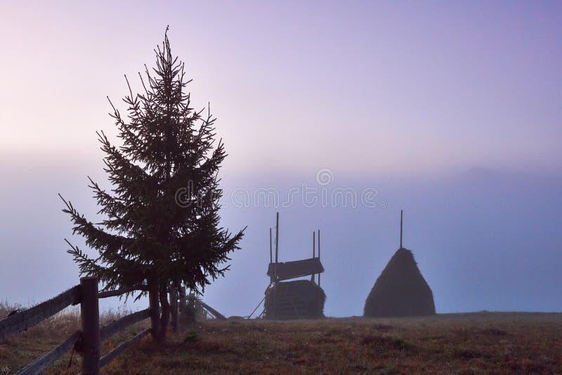 与雾和一个干草堆的惊人的山风景在秋天 图库摄影