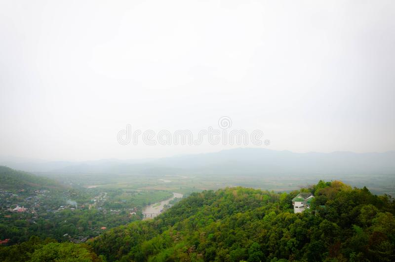 与雾的山遮暗下面城市 免版税图库摄影