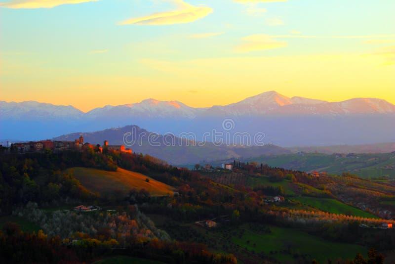 与青山和亚平宁山脉包围的小镇的风景风景 免版税库存照片