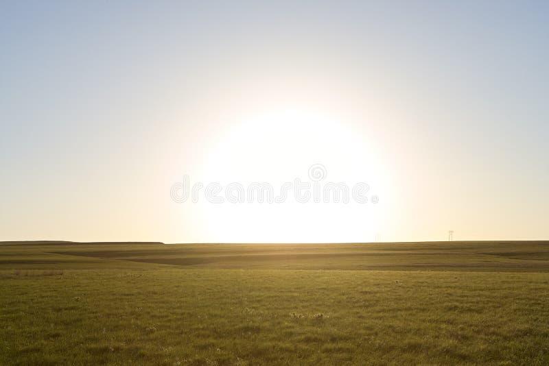 与青山的平静的农村场面在日落 免版税库存照片