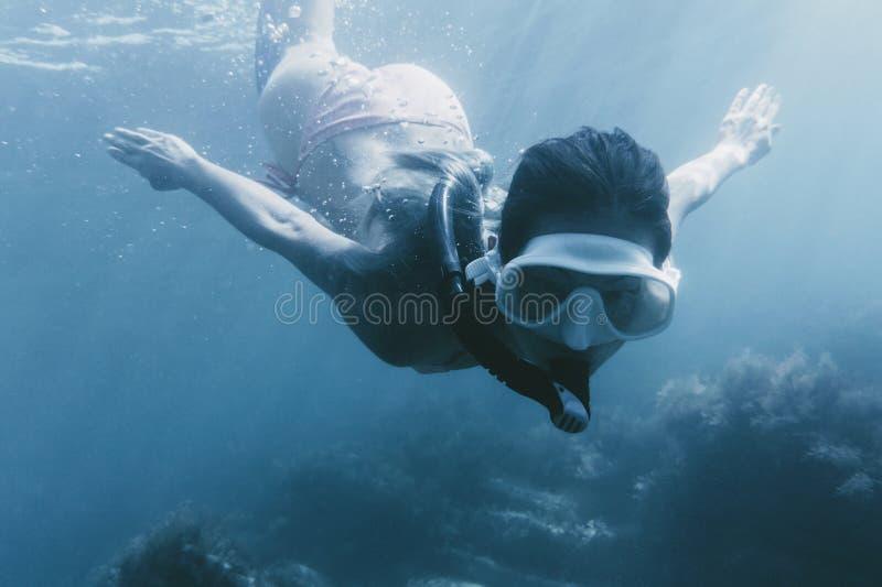 与面具和废气管的妇女游泳 库存图片