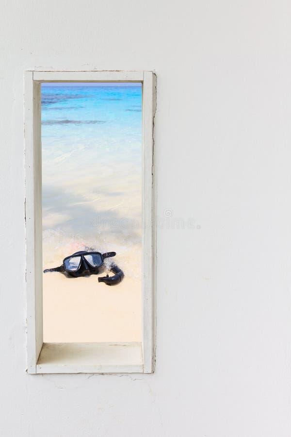 与面具废气管的白色墙壁窗口在海滩 免版税库存图片