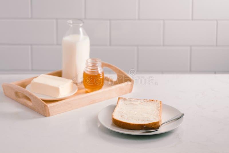 与面包切片、黄油、牛奶和蜂蜜的早餐桌 库存照片