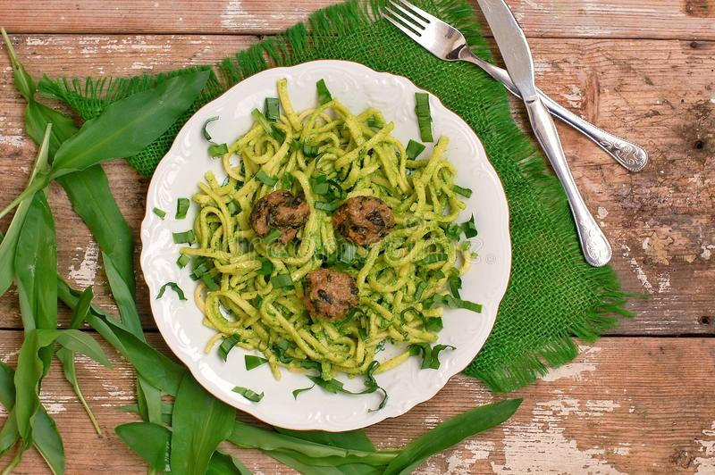 与面团、绿色pesto、丸子和硬粗布的食物在木背景的白色板材 免版税库存图片