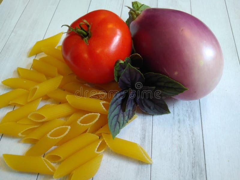 与面团和绿色蓬蒿,茄子的蕃茄 库存照片
