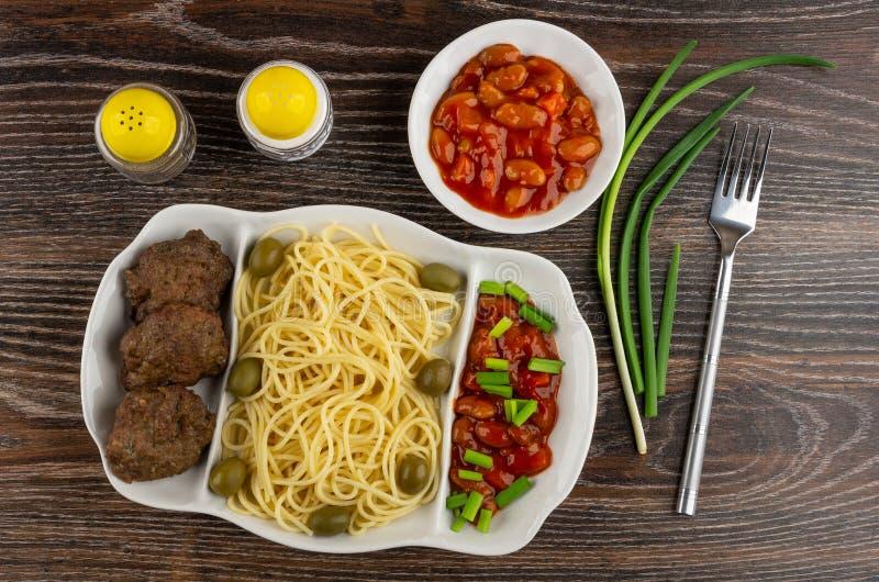 与面团,炸肉排,在蕃茄,大葱,橄榄,盐,胡椒,在桌上的叉子的豆的盘 顶视图 免版税库存照片