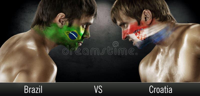 与面对面的旗子的两个足球迷 免版税库存照片