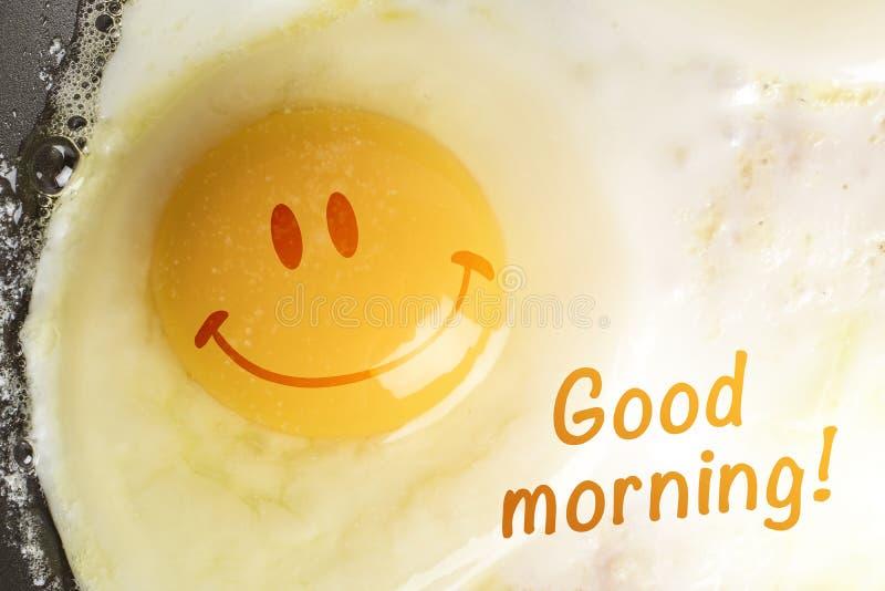 与面带笑容的荷包蛋在卵黄质和题字早晨好 库存照片