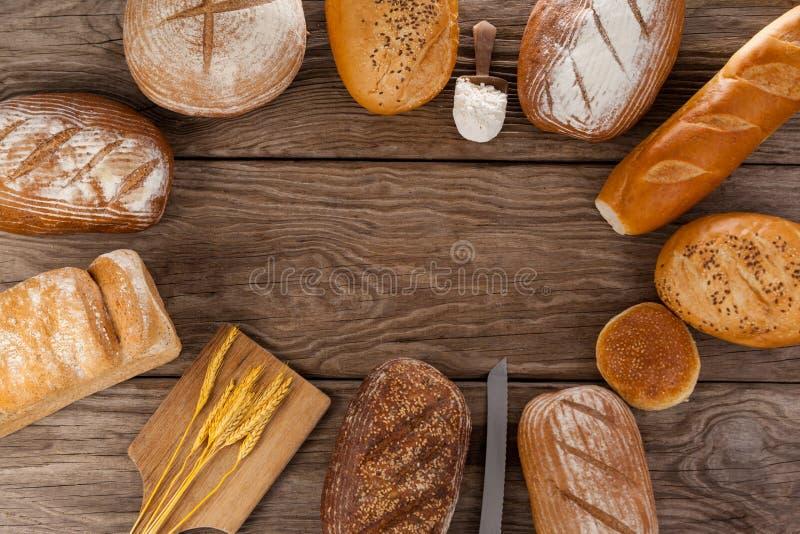 与面粉和麦子瓢的各种各样的面包大面包  免版税库存图片