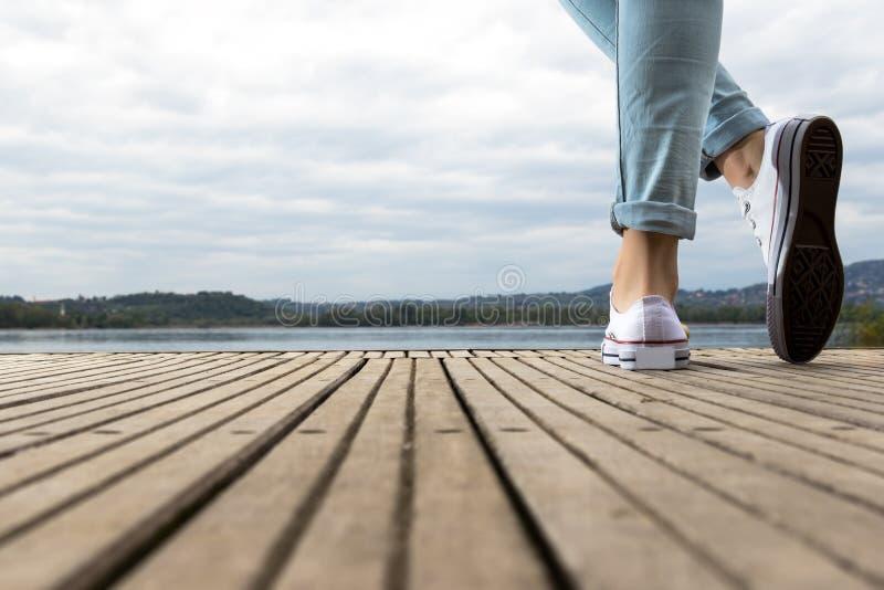 与鞋子和蓝色牛仔裤的女孩脚在一个木码头 免版税库存照片