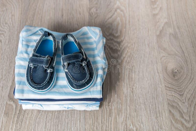 与鞋子的被折叠的蓝色和白色紧身衣裤对此灰色木背景 新出生的男孩的尿布 堆婴儿衣物 孩子o 图库摄影
