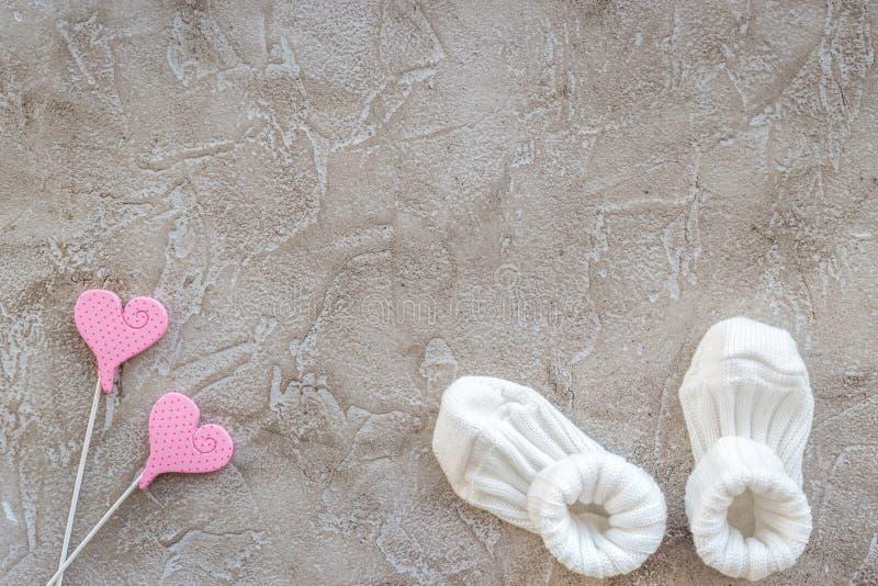 与鞋子的婴儿送礼会现代设计在灰色石背景顶视图大模型 库存照片