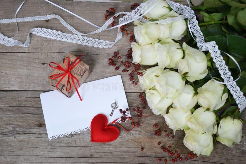 与鞋带、红色心脏、礼物盒、钥匙和纸的白玫瑰您的在木背景的文本的 免版税库存照片