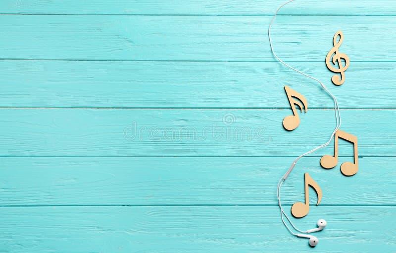 与音乐笔记、耳机和空间的平的被放置的构成文本的 免版税库存图片