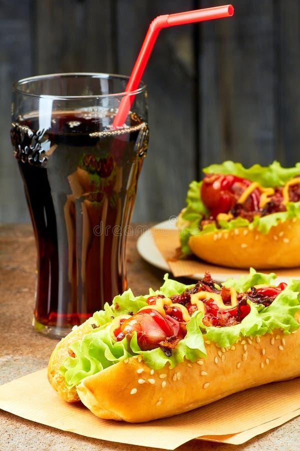 与顶部和杯的两个热狗可乐 免版税图库摄影