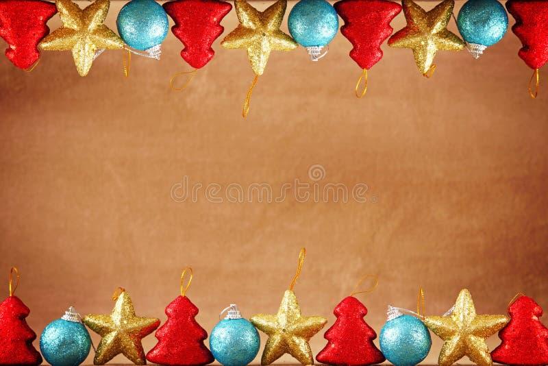 与顶面和底下边界的圣诞节或新年欢乐棕色背景由圣诞节玩具制成 免版税库存照片