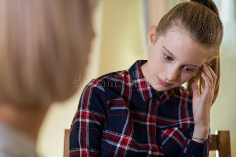 与顾问的沮丧的十几岁的女孩会谈 库存照片