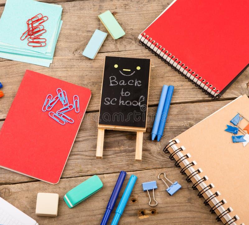 与题字& x22的木匾; 回到school& x22;近的笔记薄、纸和其他文具在棕色木桌上 免版税库存图片